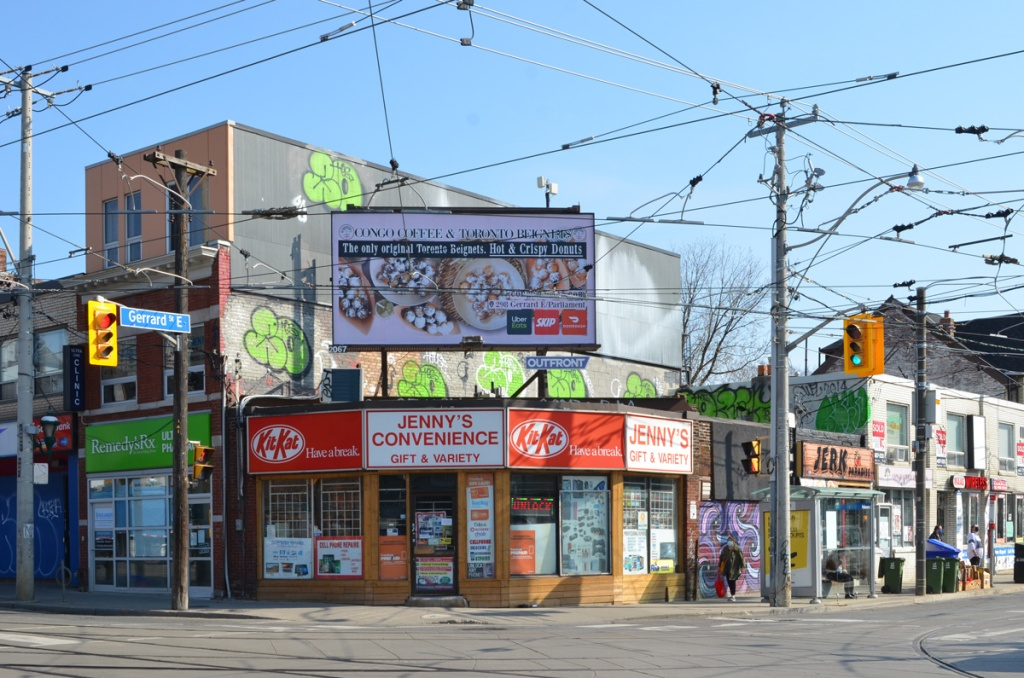northeast corner of parliament and gerrard with Jennys convenience store with its red and white sign with kit kat advertising, billboard above the store, other stores adjacent to it, Jerk restaurant, Remedy Rx,