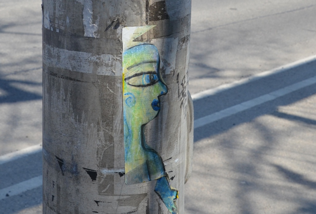 paste up graffiti on a pole, a drawing of a portrait of a woman in profile, drawn in black but shaded in blues and greens