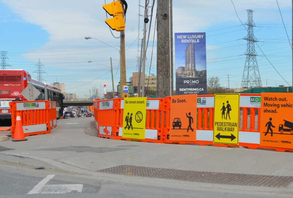 large yellow and orange signs guide pedestrian track through a busy intersection with a lot of construction