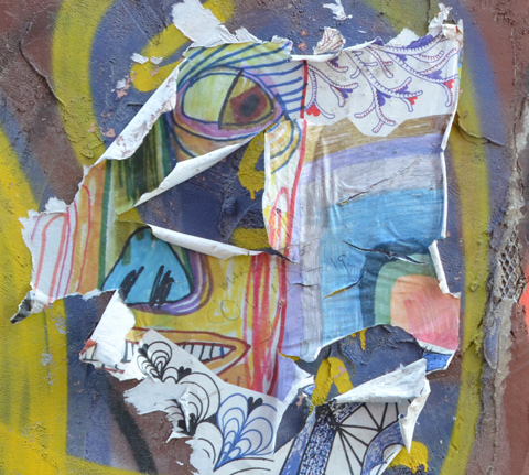 paper paste up on a wall that is badly peeling around the edges, an abstract face with blue nose and yellow skin