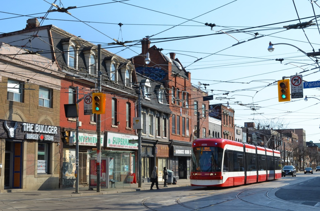 new TTC streetcar travels westbound on Queen Street East past old brick storefronts, historic buildings, The Bullger Burger snad Steak, Convenience and Supermarket, 2 people waiting to get on streetcar,