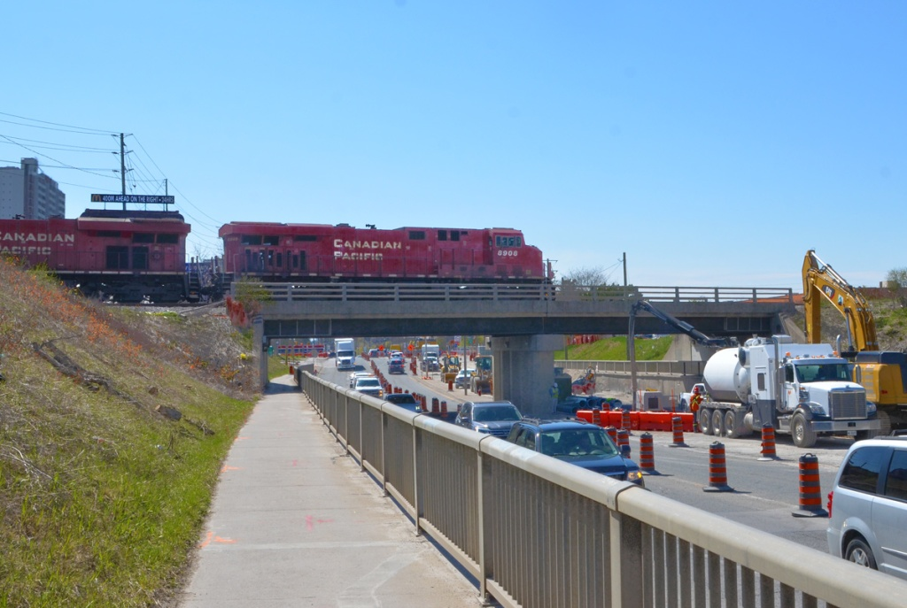 red Canadian Pacific engine pulls a train across a bridge over Finch Ave West on its way northward.  Traffic under the bridge, also some construction work, a crane and a large truck blocking some of the lanes
