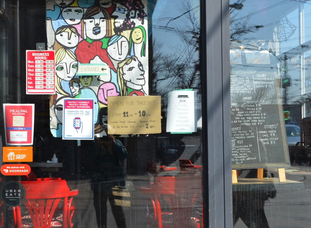 signs and pictures in the window of a restaurant, open for takeout from 11 a.m. to 10 p.m.