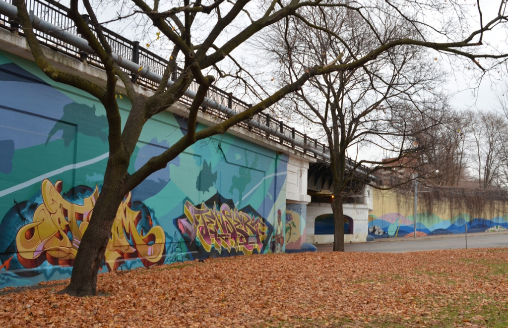 park in autumn, wall of railway embankment runs along edge of park, mural on the wall, water theme, with text throw up street art by tenser and steam