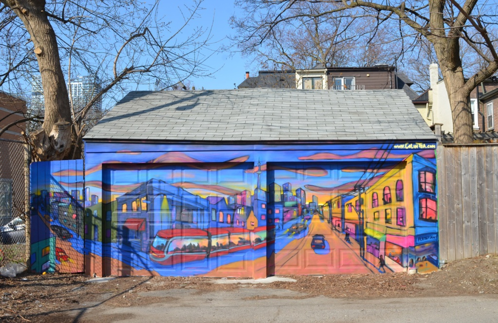 a mural of a toronto street with a TTC streetcar on it, over two garage doors in a small Cabbagetown lane