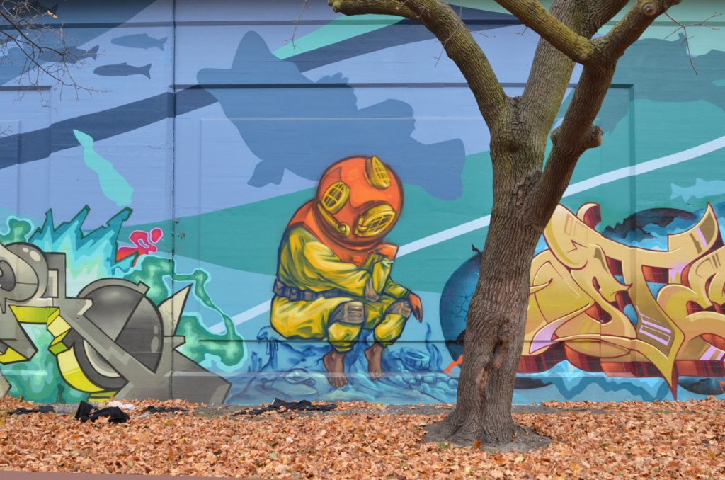 tree in front of a mural, painting of a person in vintage scuba outfit with old fashioned helmet, yellow suit, weight belt, sitting on a box or a rock at the bottom of the lake, silhouette fish swimming past