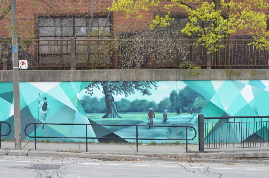 mural on Jones Ave., two pictures shown, one is a man with a backpack walking towards a TTC bus stop.  The second is kids on bikes on a path in a park