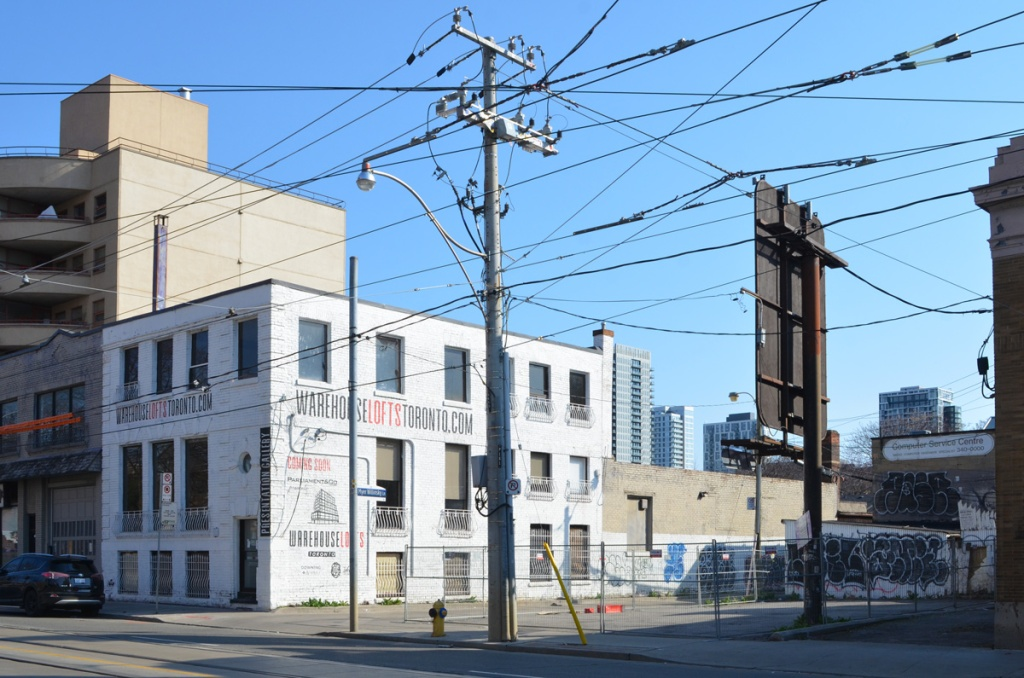 utility pole with many wires, an old brick warehouse that has been converted into loft apartments, a vacant lot surround by fence, a tall billboard seen from the back