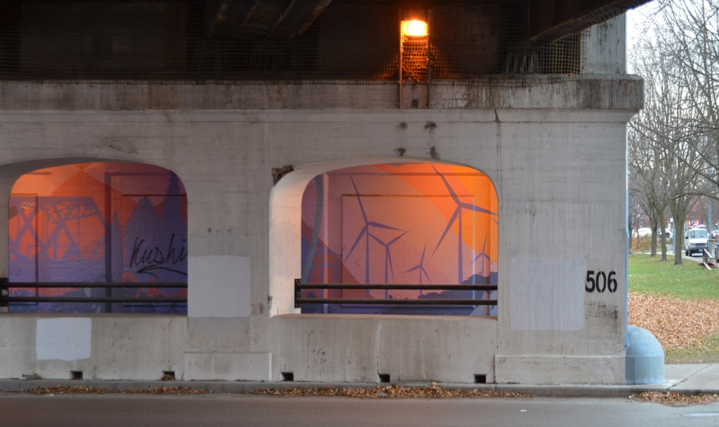 Under a railway overpass, looking across the street to arches in concrete supports between road and sidewalk, lights on above sidewalk, mural painted on the far wall including purple windmills on pink and orange background