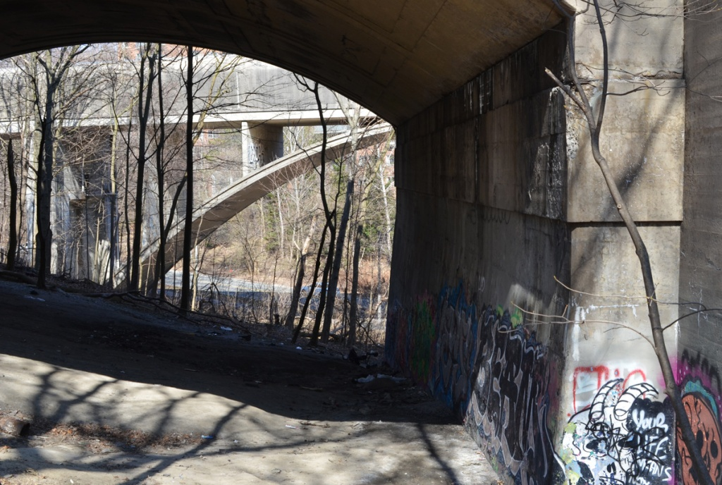 looking through arch in bridge to another bridge.  the one in the background is the covered bridge for the TTC subway between Sherbourne and Castle Frank stations