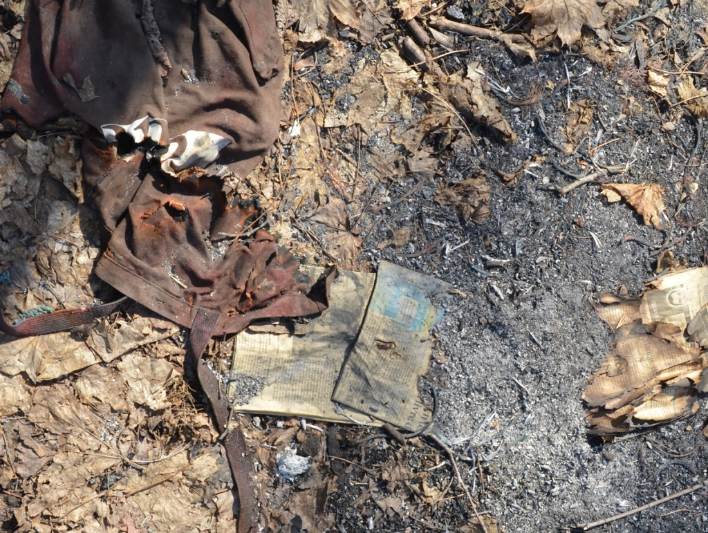 garbage on the ground, an old piece of clothing and some paper, looks like has been partially burned