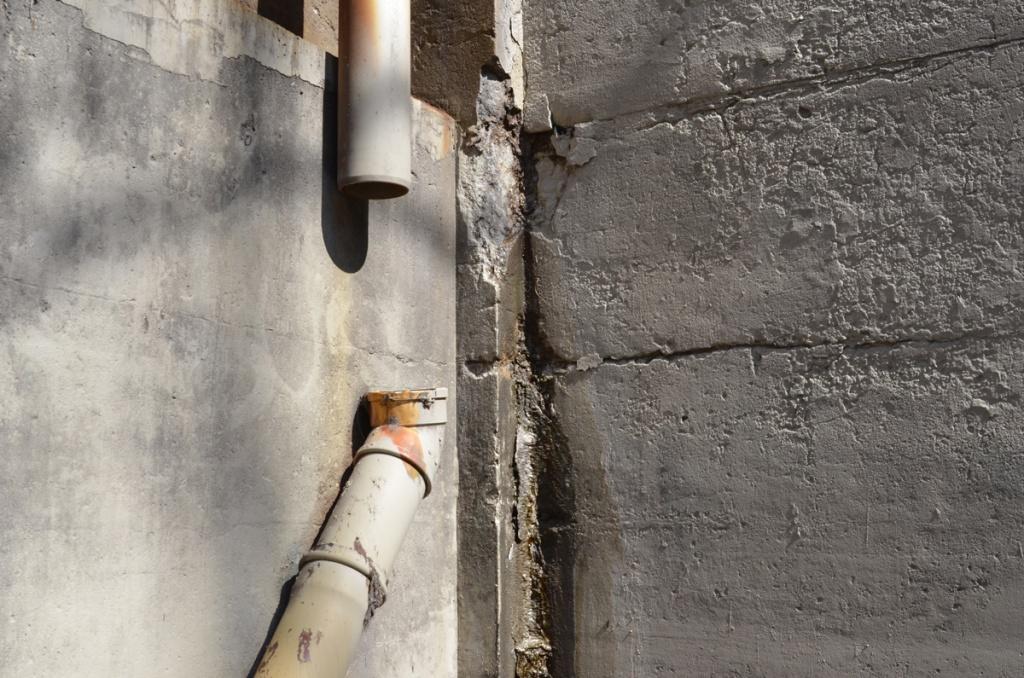 broken pipe, missing a piece, no connection, under a bridge