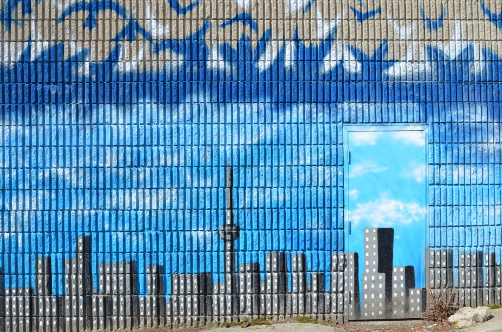 mural of blue birds flying above blue sky and CN tower and toronto skyline, exterior wall with a door in it