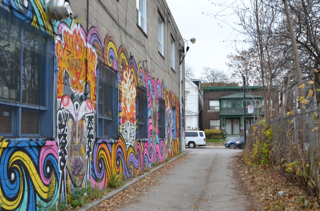 looking up an alley with a mural on the left and a chainlink fence with lots of saplings on the right