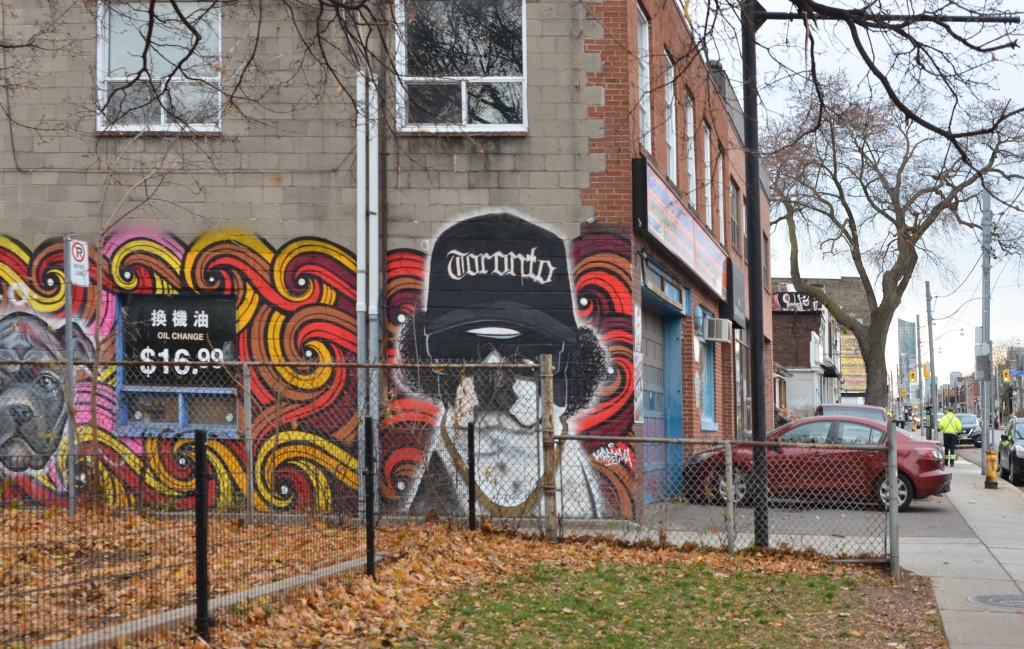 red car parked in front of a body shop with a mural on the side of its building.  Black and white dog in mural with black fuzzy ears, sunglasses and a Toronto baseball cap