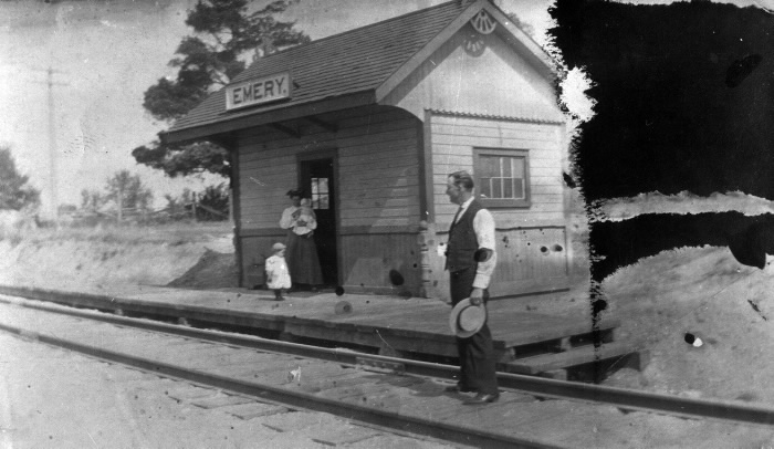 vintage black and white photo of a small wood building, Emery train station, with a woman holding a baby in the doorway and a man holding a hat in his hand standing on the tracks getting ready to flag down a train