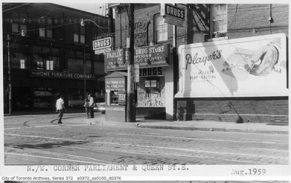 black and white photo from City Archives showing northwest corner of Parliament and Queen with the Rupert Hotel, also the Parliament Drug Store on the ground floor.  A billboard with an ad for Players cigarettes is on the wall of the building