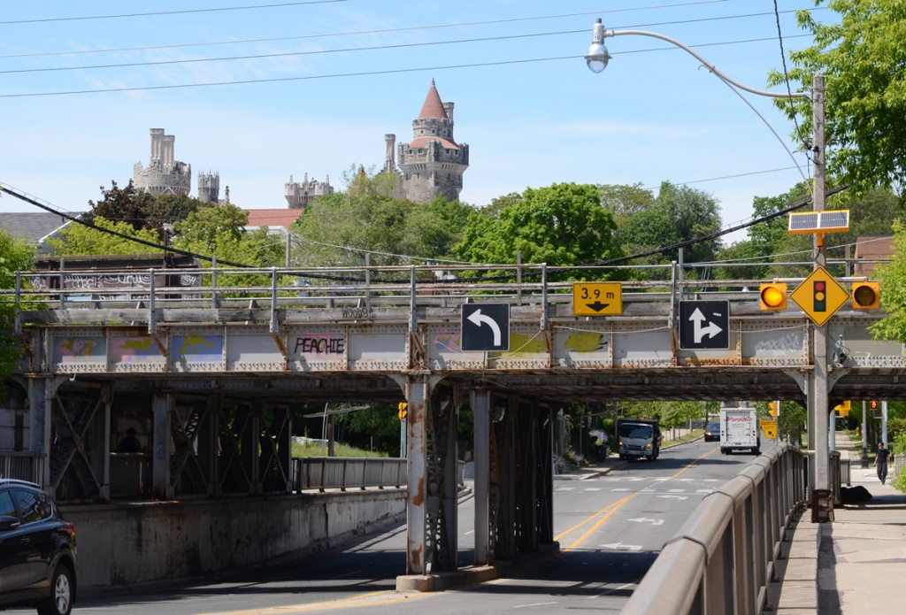 the towers and turret of Casa Loma in the background behind a railway overpass just north of Dupont.