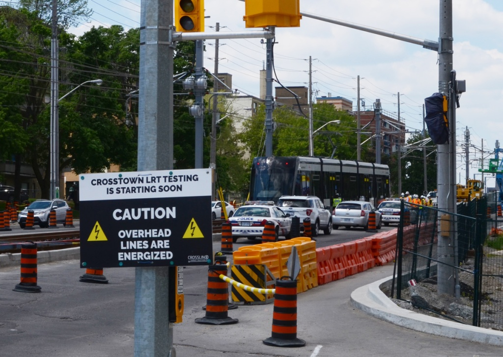 sign saying crosstown LRT testing is starting soon, caution, overhead lines are energized, on street near near new LRT train