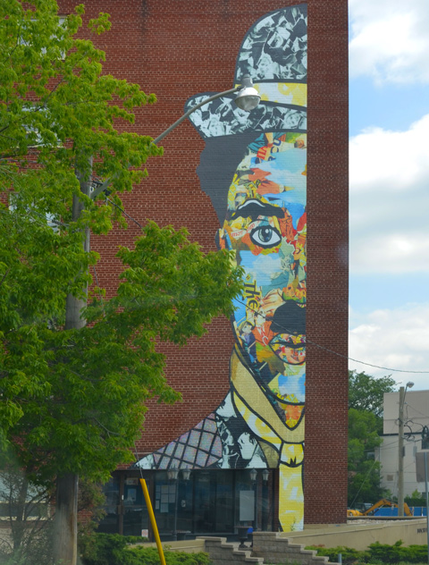 tall mural on a red brick building, left side of Charlie Chaplin's head, with hat on his head, mural in many colours and patterns