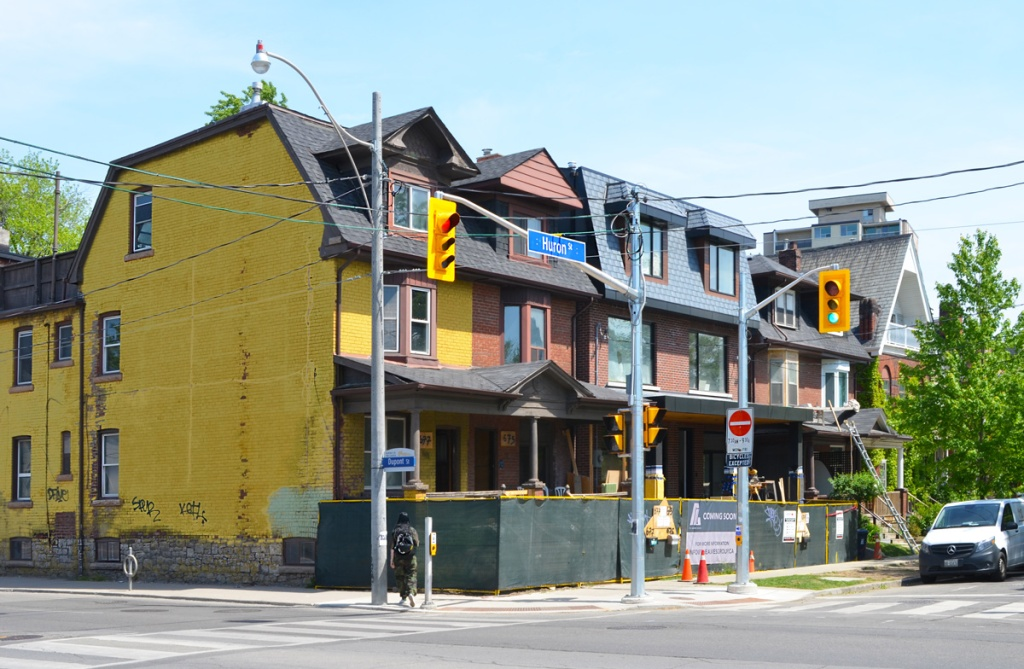 a row of three storey brick houses at Huron and Dupont with hoardings surrounding the front of the buildings.