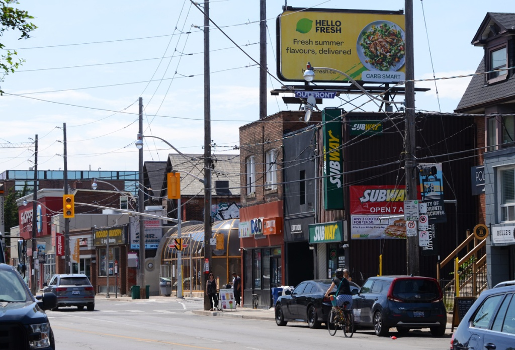 north side of Dupont, Spadina through the middle of the picture, round structure of Dupont subway station, billboard over the building on the northeast corner