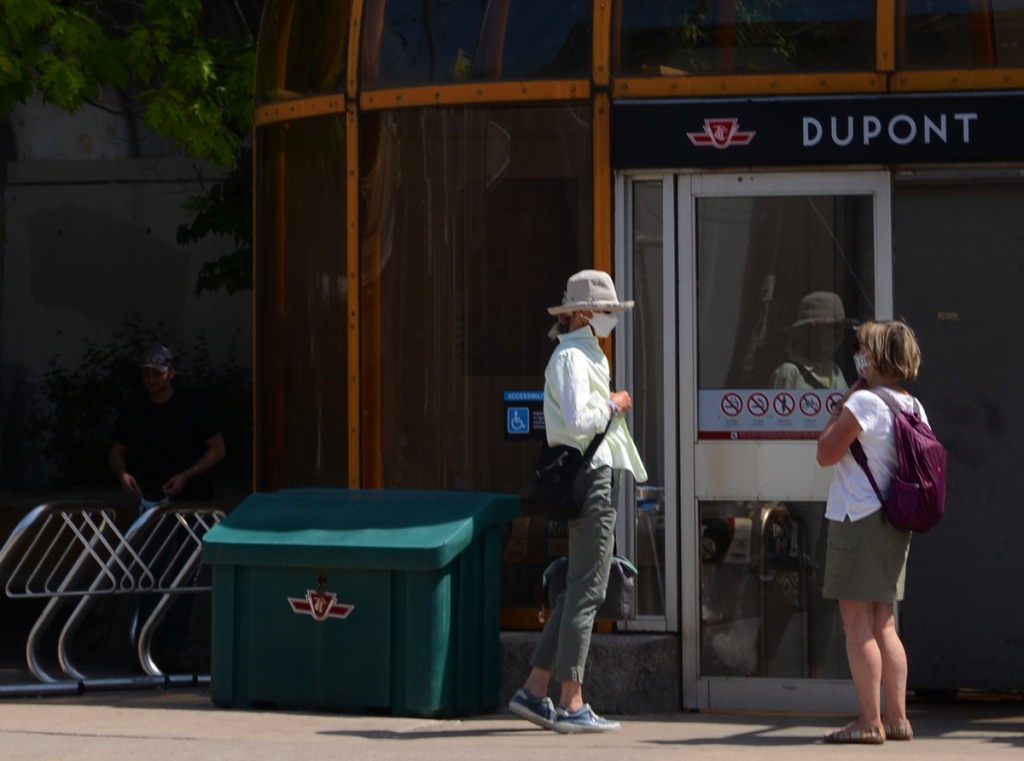 Two women stand talking outside the entrance to Dupont TTC subway station