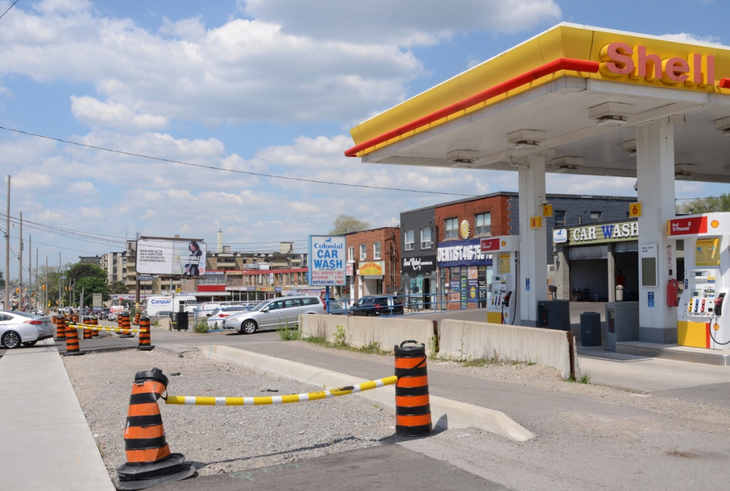 Shell service station, gas station, and other businesses on the north side of Eglinton including a car wash, a dentist office, two storey development