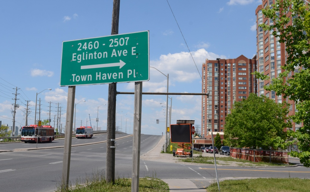 apartment buildings on north side of Eglinton, Town Haven place and traffic sign directions to parts of Eglinton not on the hill bridge