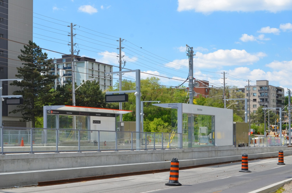New Ionview LRT station with its  protected areas, like a bus shelter, at surface level, between the lanes of traffic on Eglinton, apartment buildings in the background