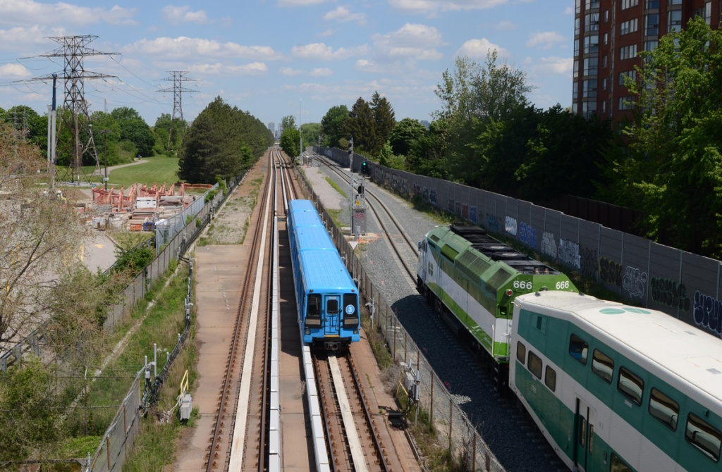 a GO train and a blue TTC subway train head north on tracks, photo taken from the bridge above