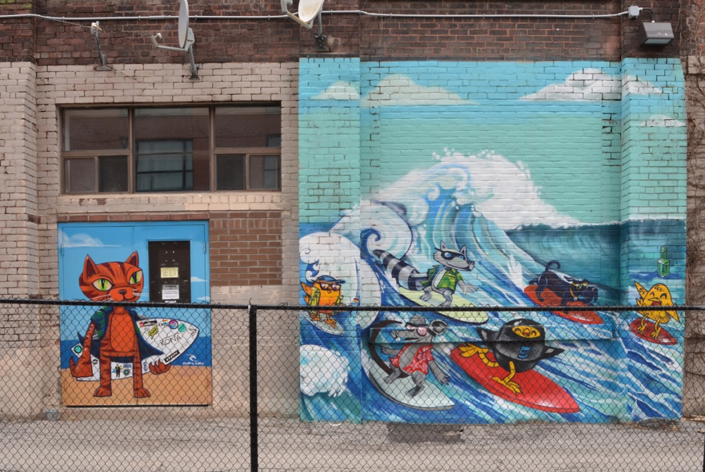 A mural by Uber 5000 in 2 parts.  on the left is a tabby cat holding a surf board.  on the right are some characters surfing, 3 yellow birdies, on in a wet suit, and three dogs.
