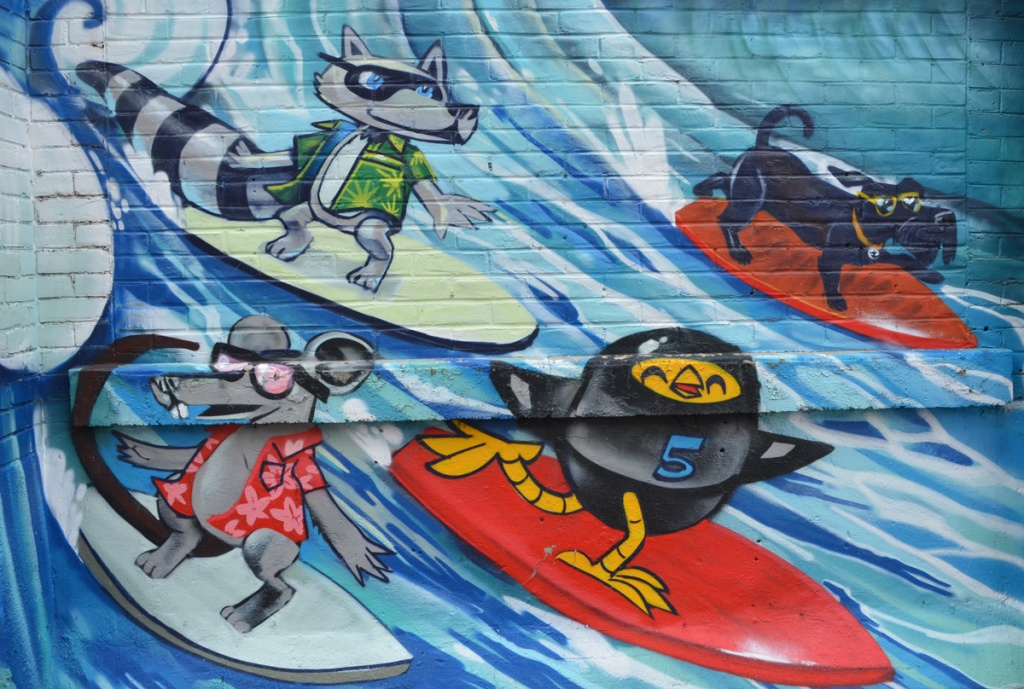 surfing mural by Uber 5000, yellow birdie in a black wet suit, a dog in a green Hawaiian shirt, a dog with goggles