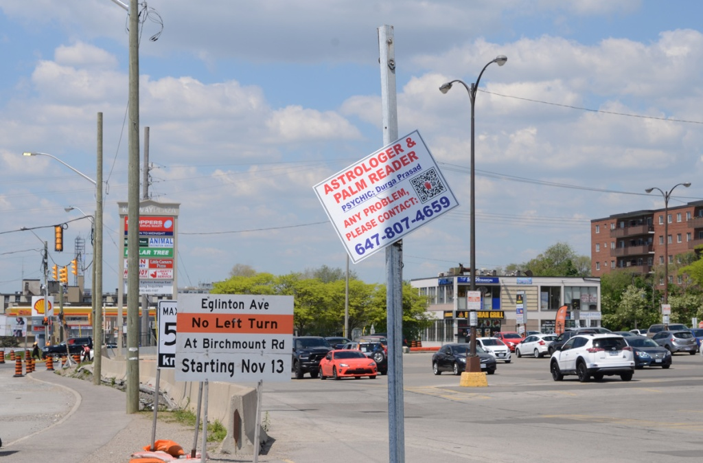 astrologer and palm reader ad as a crooked sign on a post near intersection, cars, businesses behind.  also a sign that says no left turn from eglinton onto birchmount starting November 13