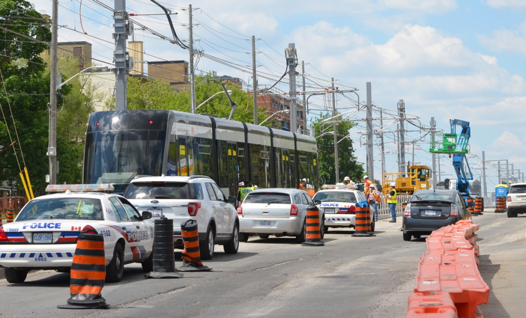 police cars and other cars parked in left lane of traffic, along side new LRT train