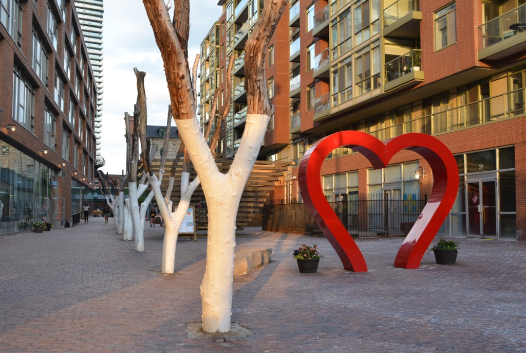 Distillery district, a line of fake trees with trunks painted white, no leaves, beside a shiny red sculpture of a large heart.  Behind that is art installation called From Small Beginnings by Jack and Charlie Leather and it is a stack of timber arranged in a large upside down pyramid