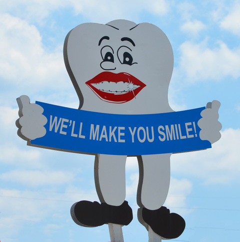 picture of a large tooth with a big red lips and shiny white teeth holding a blue banner that says we'll make you smile