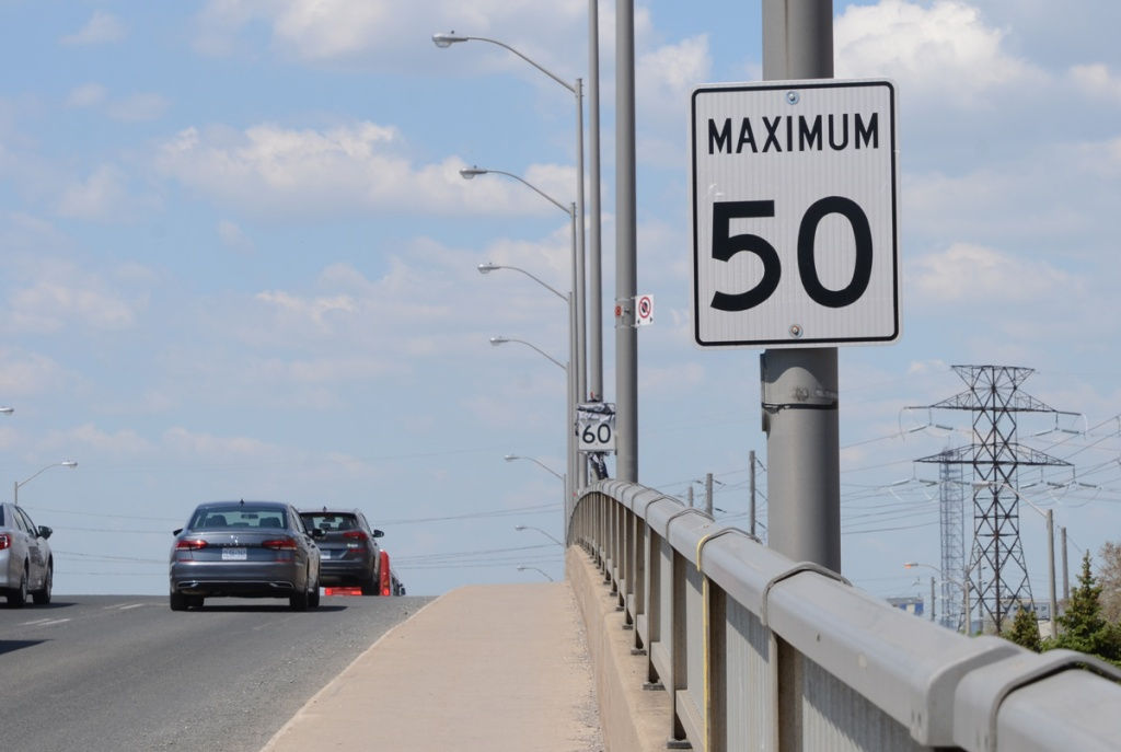 light traffic on a hill with maximum 50 sign , guardrail, hydro poles beyond,