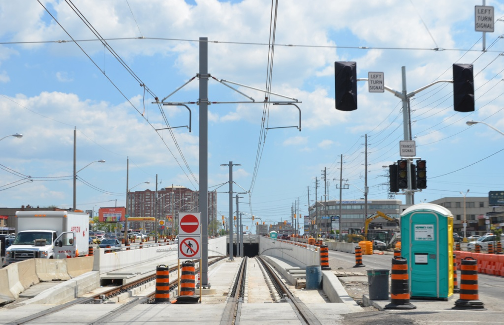 looking along new rail tracks for Crosstown LRT as they go underground just west of Kennedy station, traffic on both sides of the tracks