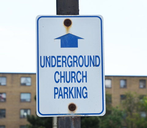 sign with an arrow pointing straight ahead and words that say underground church parking