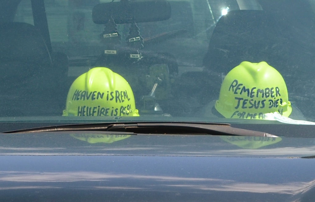 2 hard hats inside a car.  Both yellow. One says Heaven is real Hellfire is Real. and the other says Remember Jesus died for me and you