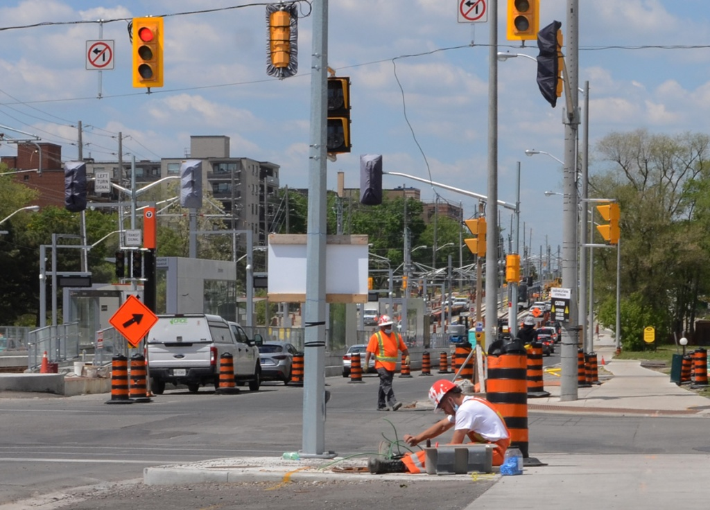 a workman sits on the sidewalk as he works with underground cables at construction site for new LRT on Eglinton