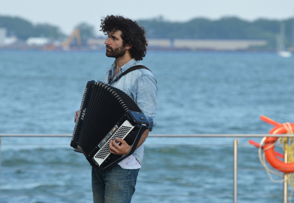 A male accordion player, Joseph Landau, stands beside the waterfront.  Curly black hair.