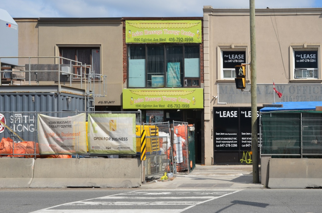 shops on Eglinton West behind construction for Crosstown, Asian Massage Therapy Center, and en empty store for lease.
