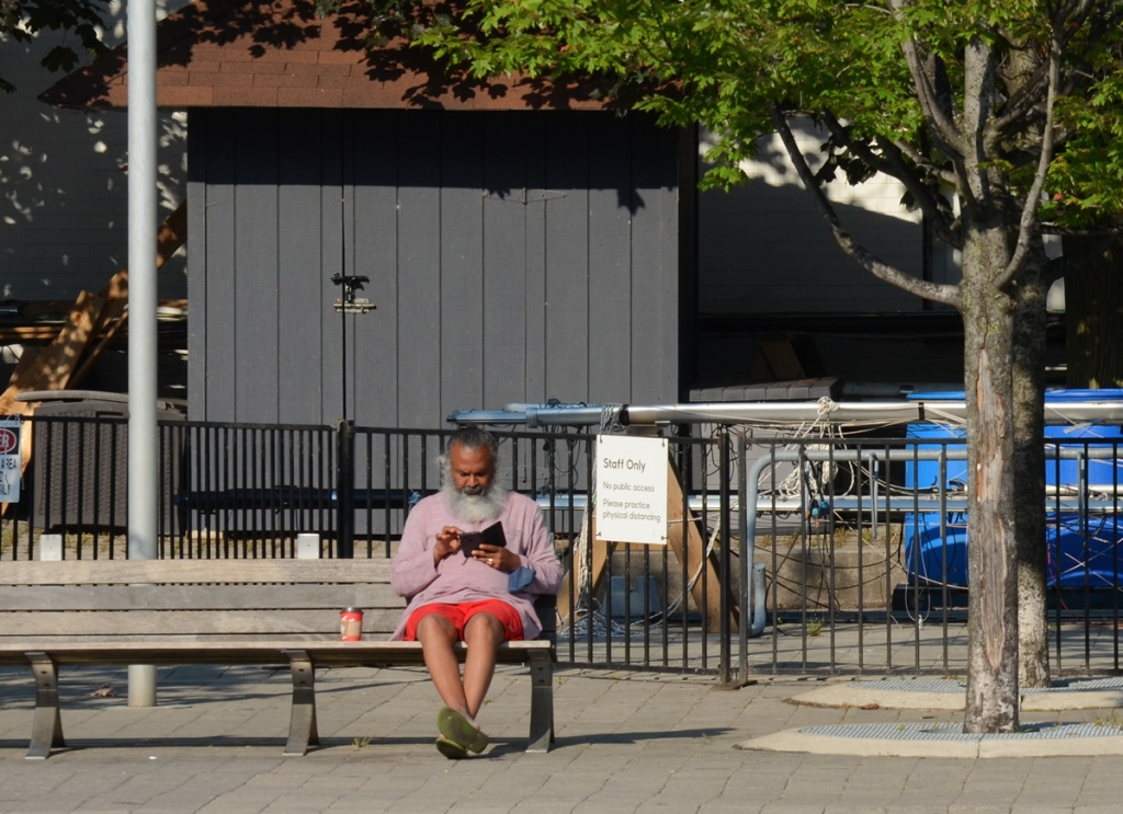 an older man with a big fluffy grey beard sits on a bench with Tim Hortons cup beside him.  He's wearing orange shorts and a pink top.  Looking at his phone