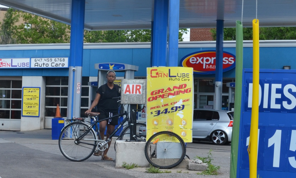 a woman dresses in black t shirt and shorts and holding her bike is getting sir from an air pump at an ultramar service center