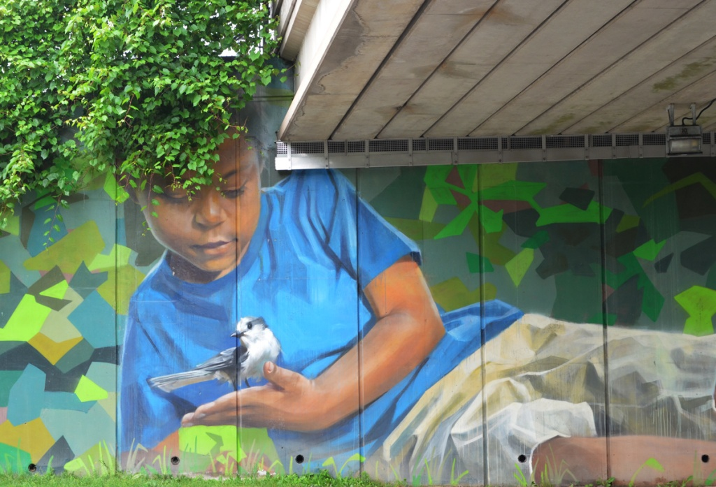 Jarus mural of a young boy with a blue jay