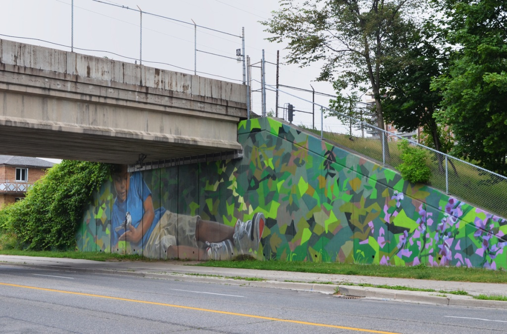 mural by Jarus of a young boy holding a blue jay bird, beside sidewalk on TTC subway underpass Pharmacy Ave in Scarborough