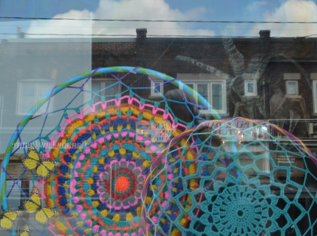 crocheted concentric circles in a window with reflections of the houses across the street