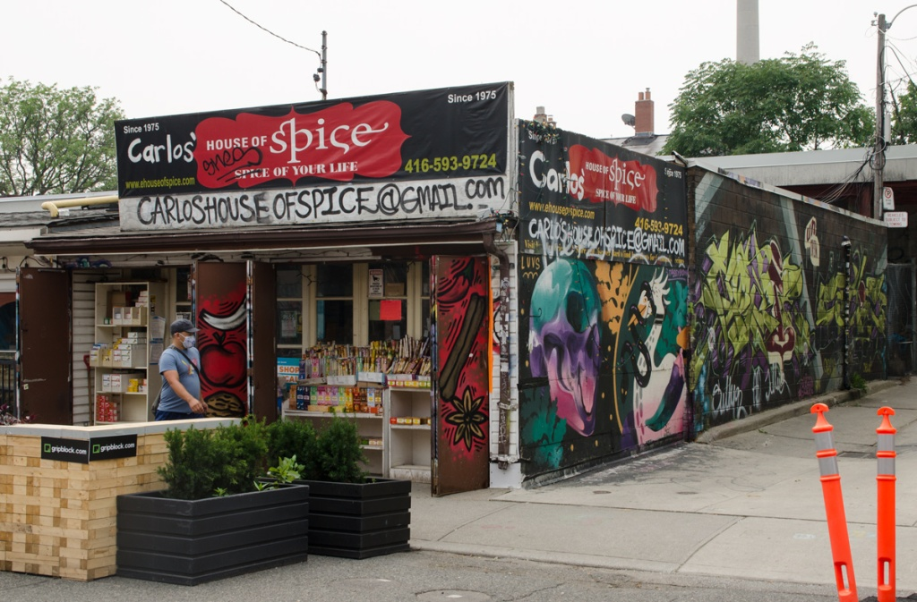 Carlos House of Spice in Kensington, with an alley beside it, murals on the walls in the alley, incense for sale in front,